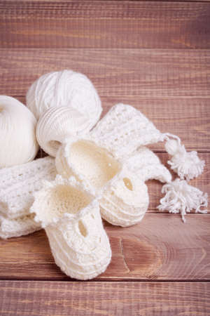 bootees: Knitting of white thread and balls on wooden boards