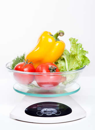 Kitchen weight scale with vegetables. Isolated on white background. photo