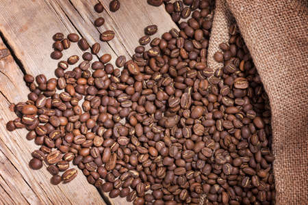 coffee beans scattered on the wooden planks photo