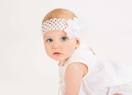 bebes ni�as: la edad de lactancia Diez meses despu�s un fondo blanco Foto de archivo
