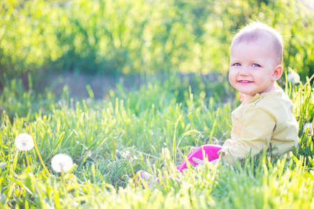 Baby eleven months months sitting in the grass