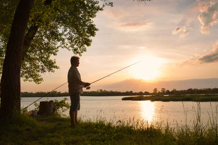 A fisherman with a fishing rod on the river bank