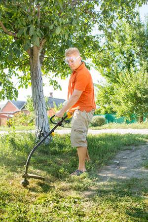 mows: A man mows a lawn mower near the house Stock Photo