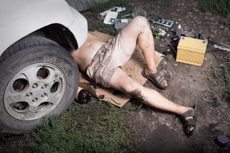 car mechanic: Mechanic lying and working under car Stock Photo