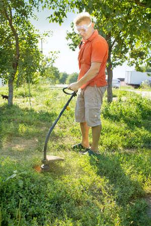 A man mows a lawn mower near the house Stock Photo
