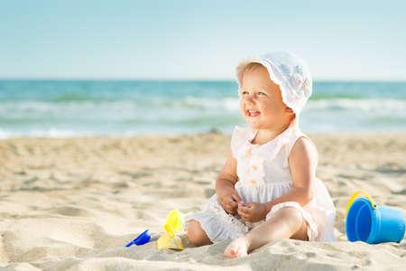 bebekler: Bebek denize yakın kumlu plajda oynarken Stok Fotoğraf