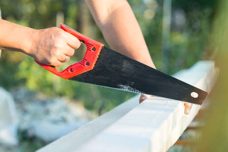 sawing: male worker sawing a board hacksaws
