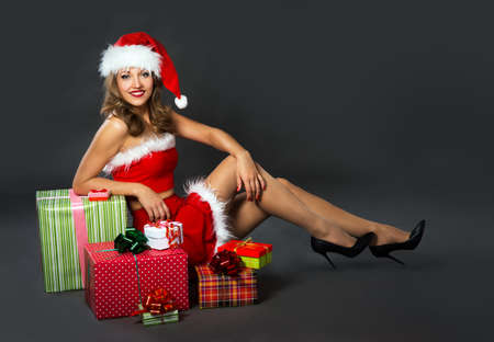 female christmas: young woman in a Christmas costume on a black background