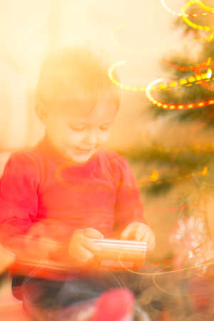 baby near christmas tree: Christmas blurred background, Happy baby near Christmas tree Stock Photo