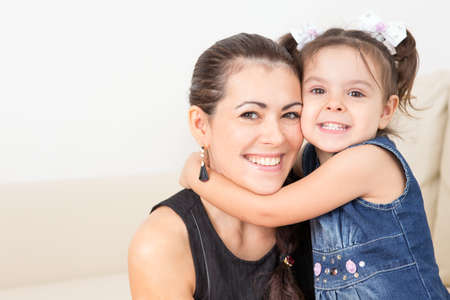 family fun: young mother with her baby on the couch