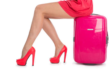 Womans legs in high heel shoes and a suitcase