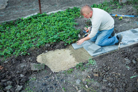 puts: Man puts paving in the garden