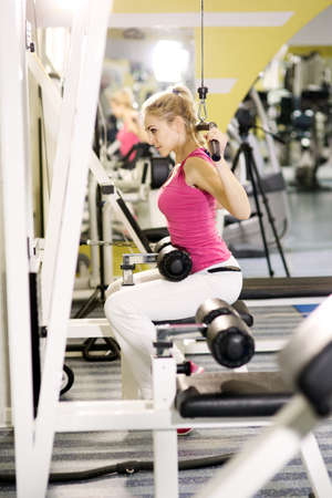 simulators: Girl is engaged on simulators in gym