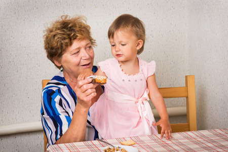 grandkids: grandmother with her granddaughter in the kitchen