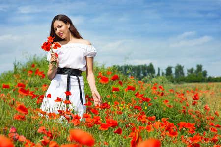 fields of flowers: Girl walks in a field of poppies Stock Photo