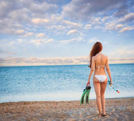 flippers: hermosa chica en un traje de baño en la playa al atardecer Foto de archivo