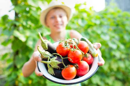 obesidad infantil: Un muchacho con un plato de verduras en el jard�n
