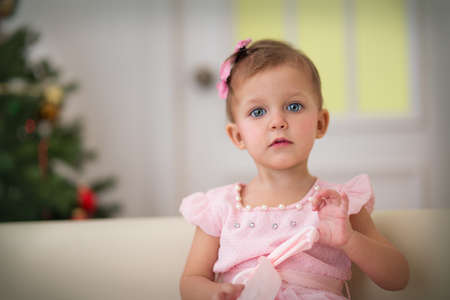 Baby age of eighteen months sitting on the couch in the room with the Christmas tree Stock Photo