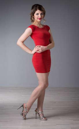 guadaña: Mujer joven con el pelo en el vestido de noche rojo Foto de archivo
