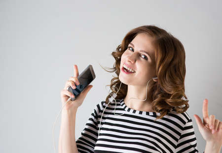 mp3 player: Young woman in headphones listening to music from the phone Stock Photo