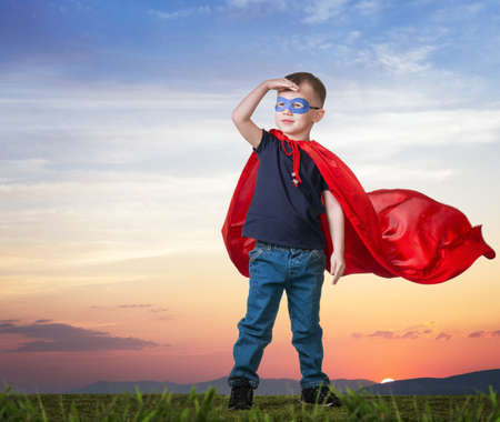 A boy in a Superman costume stands on the grass in a red cloak