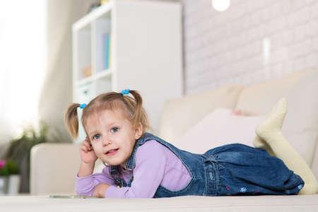 Kleines Mädchen spielt mit dem Telefon im Zimmer