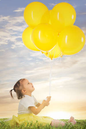 little girl wit yellow balloons on the grass