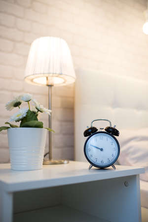 Alarm clock on the bedside table near the bed Stock Photo