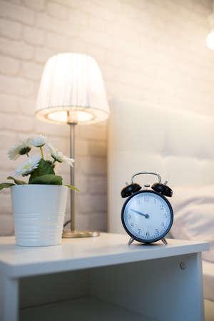 Wekker op de nachtkastje bij het bed