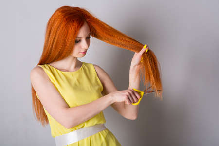 A young woman in a yellow dress wants to cut her hair