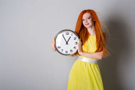 Young woman in yellow dress with big clock