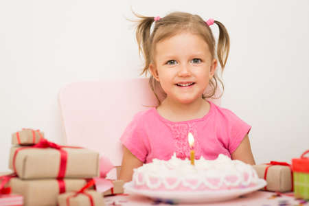 3 year old: A girl of three years old with a birthday cake