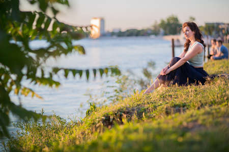 Beautiful young woman on the river bank