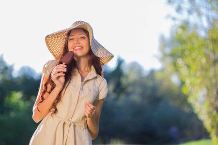 Jonge vrouw die roomijs in het park eet, vrouw die een ijslolly in aard eet Stockfoto