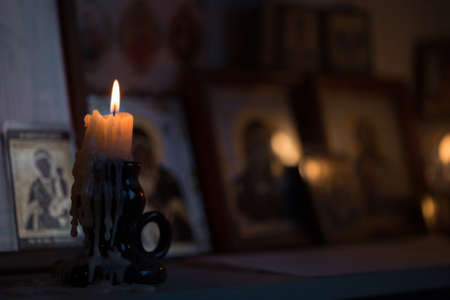 A burning candle against the background of orthodox icons in a dark room Stock Photo - 88575129