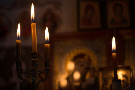 A burning candle against the background of orthodox icons in a dark room Stock Photo - 88559844