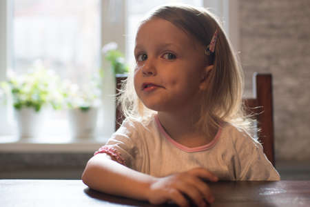 A little girl of three years is sitting at the table Stock Photo