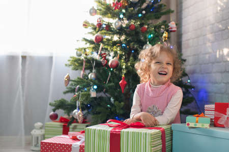 Girl playing in the room with a Christmas tree, Happy Christmas! Child three years old girl waiting for christmas
