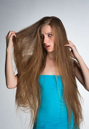 A young woman with long hair can not comb her hair, is very confused and brittle Фото со стока