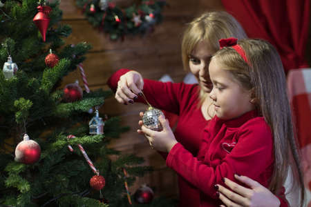 Mom and daughter meet a happy Christmas , family in a room with Christmas fir tree and gifts