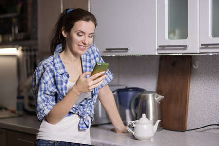 Young woman in the kitchen with the phone, the housewife is resting in the kitchen Stock Photo