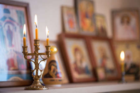 A burning candle against the background of orthodox icons Stock Photo