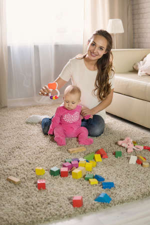 A young mother plays with a baby. A woman plays with a baby eight months of age Banque d'images
