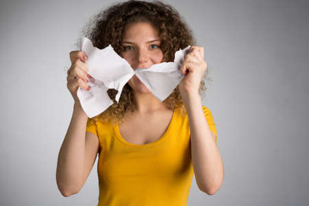 A woman in a yellow T-shirt furiously tore the paper, Woman tearing paper