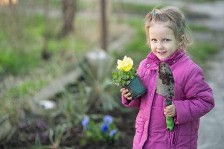 The girl helps plant flowers in the garden Reklamní fotografie