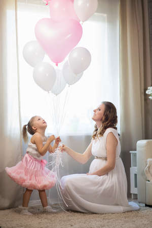 Pregnant woman with a girl of three years and balloons