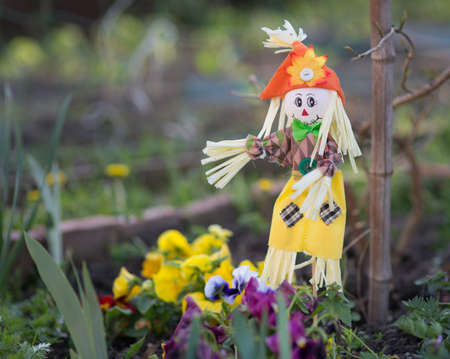Scarecrow on a flower bed with flowers