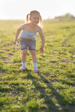 The girl is three years old, child on the field at sunset