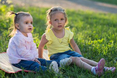 Dos niñas de dos y cuatro años sentados en la naturaleza en la hierba Foto de archivo