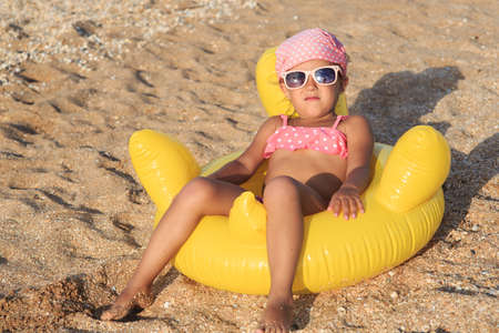 A girl of four years is resting on the sea